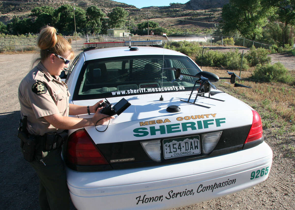 This undated photo provided by the Mesa County, Colo., Sheriff's Department, Deputy Amanda Hill of the Mesa County Sheriff's Office in Colorado prepares to use a Draganflyer X6 drone equipped with a video camera to help search for a suspect in a knife attack in Mesa County, Colo.