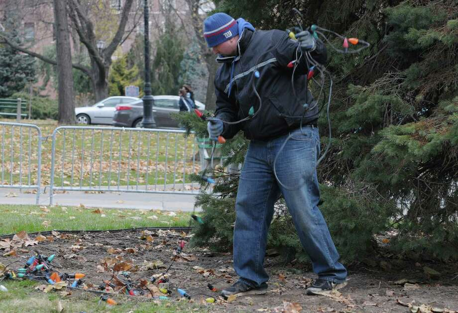 George Stegmann untangles a string of lights  as a crew from OGS strung lights on the Christmas tree on the east side of the capitol on Monday, Nov. 26, 2012 in Albany, NY.  There are two trees set up for the holiday outside the capitol, this one on the east lawn and the other tree is on the Empire State Plaza. (Paul Buckowski / Times Union) Photo: Paul Buckowski  / 00020247A