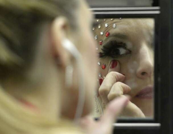 A pole dancer puts on make-up on backstage during the Miss Pole Dance Argentina and South America 2012 competition in Buenos Aires on November 26, 2012. AFP PHOTO / Juan MabromataJUAN MABROMATA/AFP/Getty Images Photo: JUAN MABROMATA, AFP/Getty Images / AFP