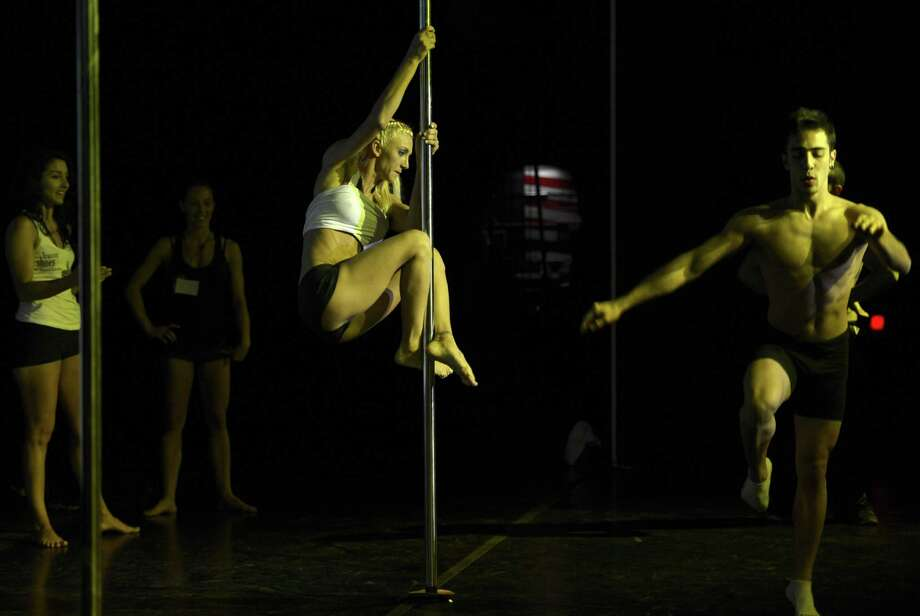 Pole dancers test the pole backstage during the Miss Pole Dance Argentina and South America 2012 competition in Buenos Aires on November 26, 2012. AFP PHOTO / Juan MabromataJUAN MABROMATA/AFP/Getty Images Photo: JUAN MABROMATA, AFP/Getty Images / AFP