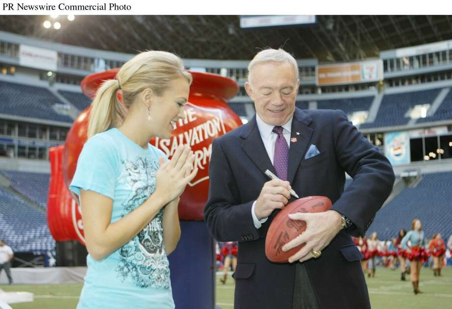 Carrie Underwood, left, is greeted by Dallas Cowboys Owner and General Manager Jerry Jones, right, at Texas Stadium. Underwood, who won Favorite New Breakthrough Artist at last night's American Music Awards, will perform during the nationally televised Cowboys Thanksgiving Day game live halftime show to kick off The Salvation Army's Red Kettle Christmas Campaign.  (PRNewsFoto/The Salvation Army, Mike Fuentes) (PR NEWSWIRE)