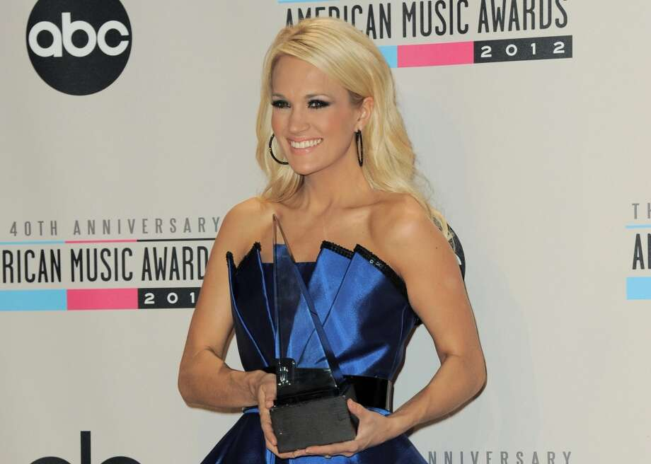 Carrie Underwood poses backstage with the award for favorite country music album for Blown Away at the 40th Anniversary American Music Awards on Sunday, Nov. 18, 2012, in Los Angeles. (Photo by Jordan Strauss/Invision/AP) (Jordan Strauss/Invision/AP)