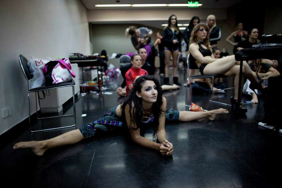 Participants of the Miss Pole Dance South America 2012 and Pole Dance Argentina 2012 watch in backstage the performance of fellow competitors in Buenos Aires, Argentina, Monday, Nov. 26, 2012. (AP Photo/Natacha Pisarenko) Photo: Natacha Pisarenko, Associated Press / AP