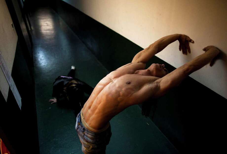 Pole dancer Carlos Franca, of Brazil, stretches in backstage before performing in the South American Male category of the Miss Pole Dance South America 2012 competition in Buenos Aires, Argentina, Monday, Nov. 26, 2012. (AP Photo/Natacha Pisarenko) Photo: Natacha Pisarenko, Associated Press / AP