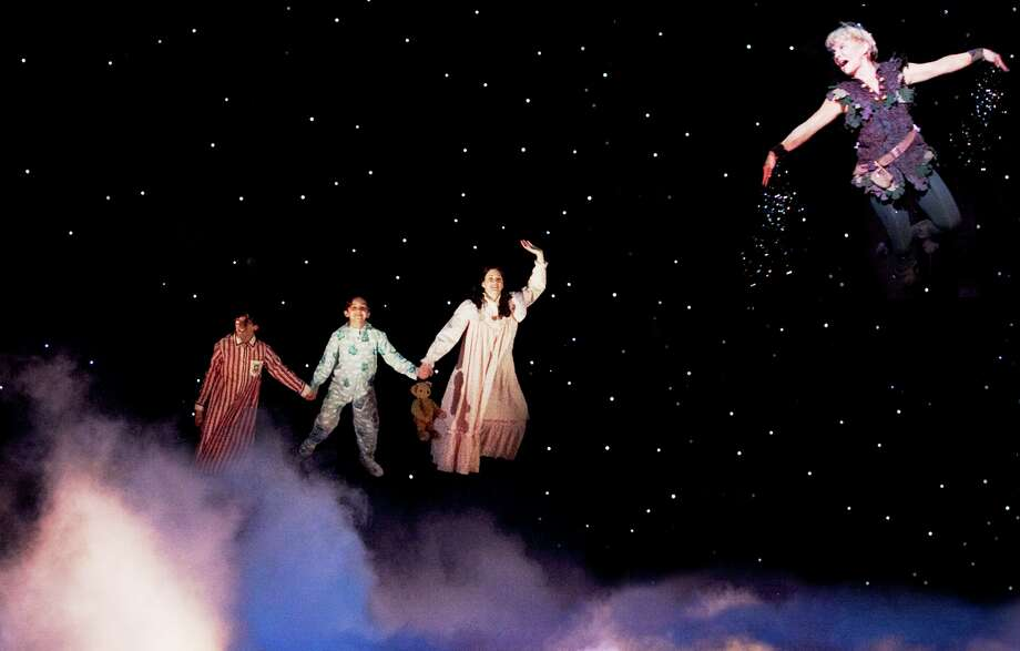 """As the title character, Cathy Rigby takes the Darling chldren (from left, Cade Canon Ball, Julia Massey, Krista Buccellato) for a spin in the stge version of """"Peter Pan."""" Photo: Courtesy Isaac James"""
