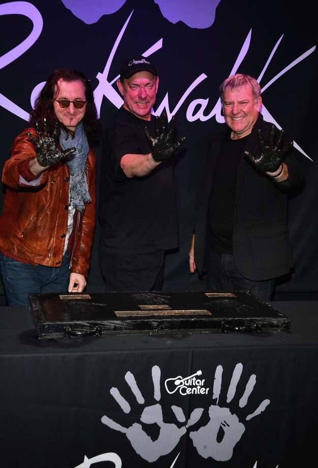 Rush members (from left) Geddy Lee, Neil Peart and Alex Lifeson were honored on Guitar Center's RockWalk this month in Hollywood. Getty Images Photo: Frazer Harrison, Getty Images / 2012 Getty Images