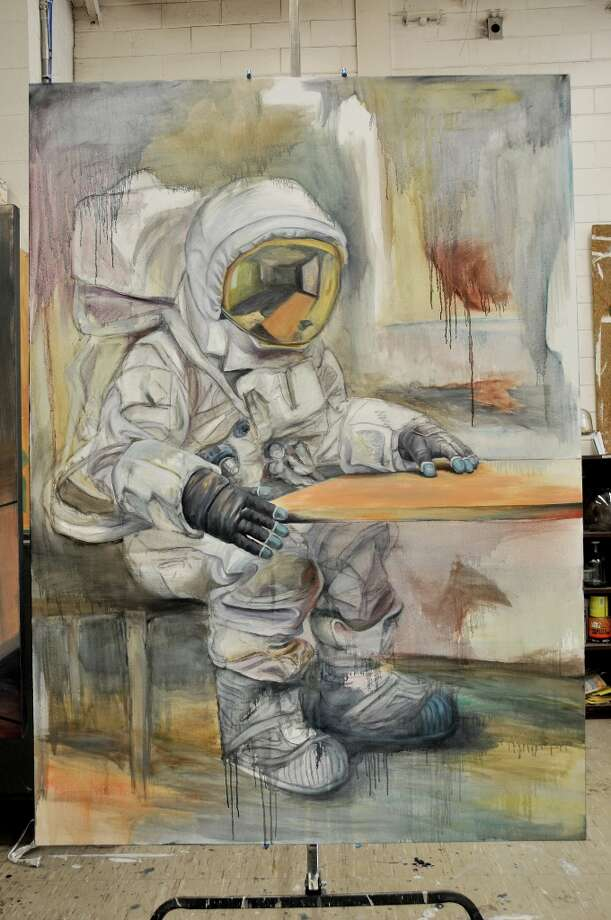 """""""Table for One"""" by Caleb Sims. """"My series of large oil paintings explore the theme of isolation,"""" Sims said. """"The astronaut suit symbolizes a contradiction between the security of the suit and the isolation it causes by separating the wearer from all outside interaction."""""""