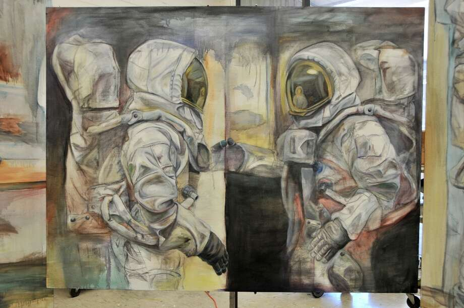 """Touching Thumbs"" by Caleb Sims. ""My series of large oil paintings explore the theme of isolation,"" Sims said. ""The astronaut suit symbolizes a contradiction between the security of the suit and the isolation it causes by separating the wearer from all outside interaction."""