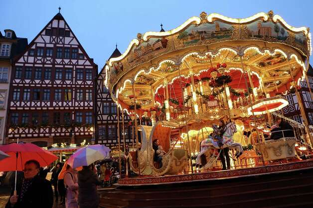 FRANKFURT, GERMANY - NOVEMBER 26:  People ride a carousel at the annual Christmas market in the city center on its opening day on November 26, 2012 in Frankfurt, Germany. Christmas markets, with their stalls selling mulled wine, Christmas tree decorations and other delights, are an integral part of German Christmas tradition, and many of them opened across Germany today. Photo: Hannelore Foerster, Getty Images / 2012 Getty Images