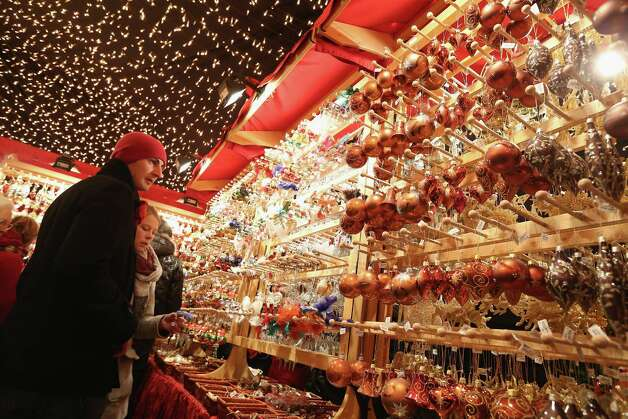 BERLIN, GERMANY - NOVEMBER 26:  Visitors look at Christmas decorations for sale at the Kaethe Wohlfahrt stand at the annual Christmas market at Gendarmenmarkt on its opening day on November 26, 2012 in Berlin, Germany. Christmas markets, with their stalls selling mulled wine, Christmas tree decorations and other delights, are an integral part of German Christmas tradition, and many of them opened across Germany today. Photo: Sean Gallup, Getty Images / 2012 Getty Images