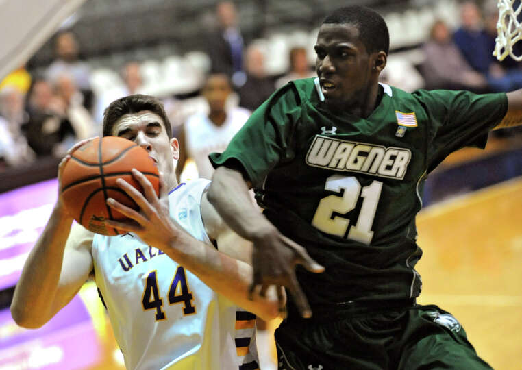 UAlbany's John Puk drives to the basket agaisnt Wagner's Orlando Parker during a basketball game at