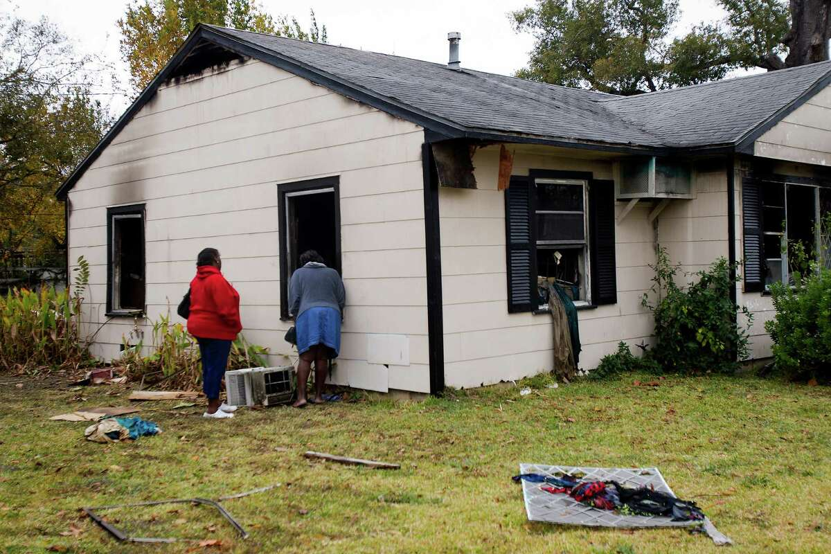 """Juliet Cotton, left, and her sister Patrice Cotton, right, look at their mother's home after the deadly fire. """"She was a very loving woman,"""" Juliet said. """"Anytime anyone needed help in the neighborhood, she would help them."""""""