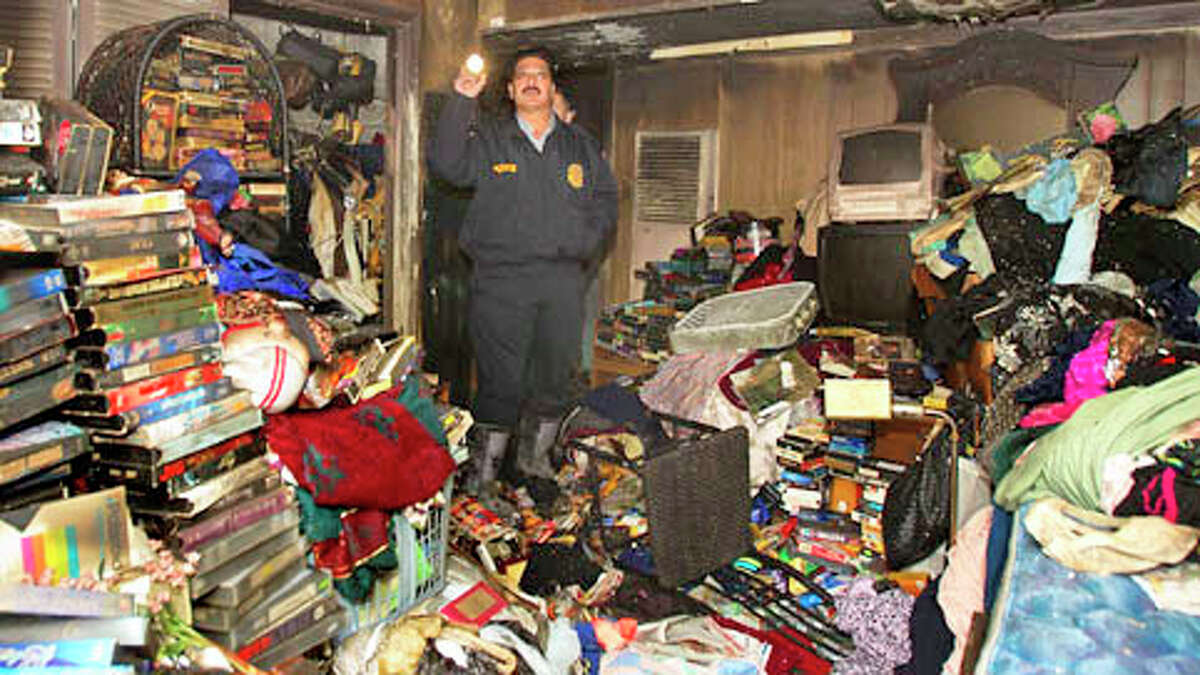 An investigator looks inside the home Tuesday after a fire erupted late Monday night in the 6100 block of Sherwood near Tolnay.