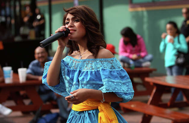 Sandy Rogriguez, 15, sings during a show at El Mercado Square on Friday, Nov. 23, 2012. Rodriguez is part of Network for Young Artists founded by retired educator Terry Lowry who started the organization 14 years ago. The organization helps aspiring musicians get opportunities to perform and raise their self-esteem in the process. Photo: Kin Man Hui, San Antonio Express-News / ©2012 San Antonio Express-News