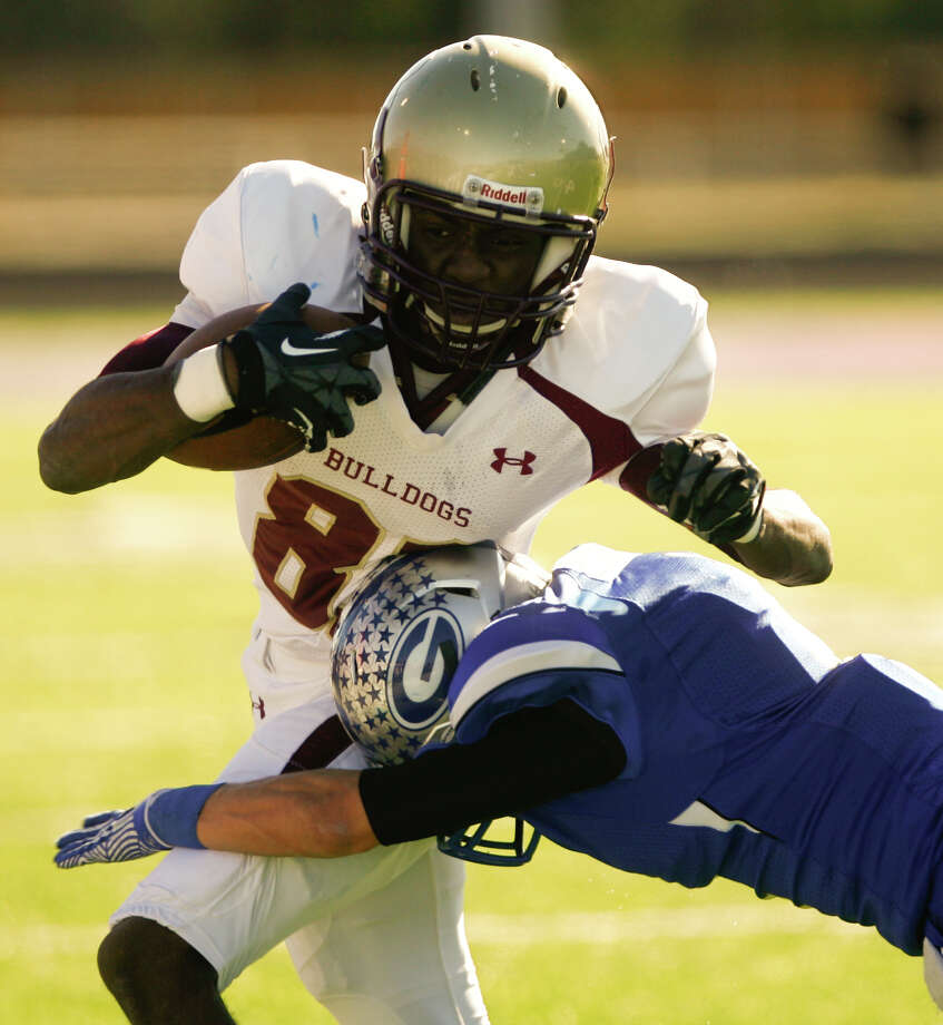 DeQuann Ruffin tries to shrug off Georgetown High School's Matt Sanchez' tackle during the second quarter of the Bulldog's 38-21 loss in the Class 4A Division I area round playoff in College Station. Photo: Nick De La Torre, Staff / © 2012  Houston Chronicle