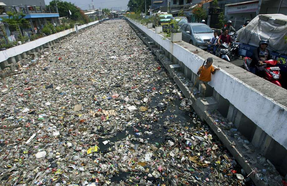 Fine for littering: In Jakarta, a scavenger fishes for recyclables in a canal that looks more like a landfill than a waterway. Photo: Tatan Syuflana, Associated Press