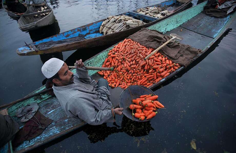 Tuber float:A Kashmiri vendor weighs carrots for sale at the floating vegetable market on Dal Lake. The aquatic market  in Srinagar, India, offers a variety of veggies grown year-round in the lake's floating gardens. Photo: Dar Yasin, Associated Press