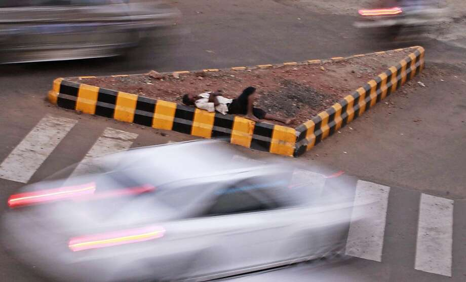 A nice, quiet place to catch some Z's:A street divider serves as a bed in Bhubaneswar, India. Photo: Biswaranjan Rout, Associated Press