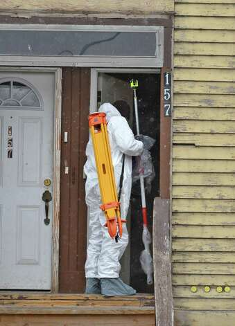 An APD crime scene investigator enters 157 Myrtle Avenue in Albany Tuesday Nov. 27, 2012, where a man stabbed three women yesterday killing one.  (John Carl D'Annibale / Times Union) Photo: John Carl D'Annibale / 00020273A