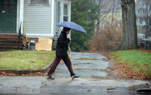 A woman walks down Seymour Avenue in Derby, Conn. Tuesday, Nov. 27, 2012. Photo: Autumn Driscoll / Connecticut Post