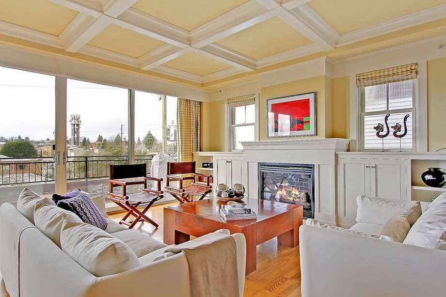 Living room of 1414 1st Ave. W., Unit 402. The 2,251-square-foot condo, built in 2004, has three bedrooms and 2.5 bathrooms -- including a master suite with a double-sided fireplace, French doors, and his and her closets -- coffered ceilings, custom millwork, air conditioning and a balcony. It's listed for $1.225 million. Photo: Courtesy Jan Selvar/Windermere Real Estate