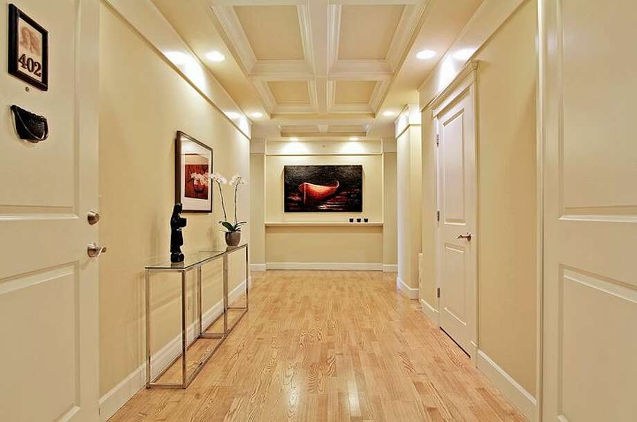 Entry of 1414 1st Ave. W., Unit 402. The 2,251-square-foot condo, built in 2004, has three bedrooms and 2.5 bathrooms -- including a master suite with a double-sided fireplace, French doors, and his and her closets -- coffered ceilings, custom millwork, air conditioning and a balcony. It's listed for $1.225 million. Photo: Courtesy Jan Selvar/Windermere Real Estate