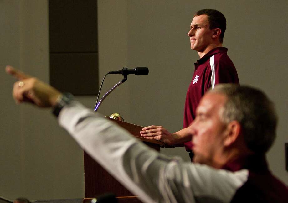 Alan Cannon of Texas A&M sports information, front, directs traffic as Texas A&M quarterback Johnny Manziel does his first press conference, Tuesday, Nov. 27, 2012, in the Bright Football Complex on the Texas A&M campus in College Station. Photo: Nick De La Torre, Houston Chronicle / © 2012  Houston Chronicle