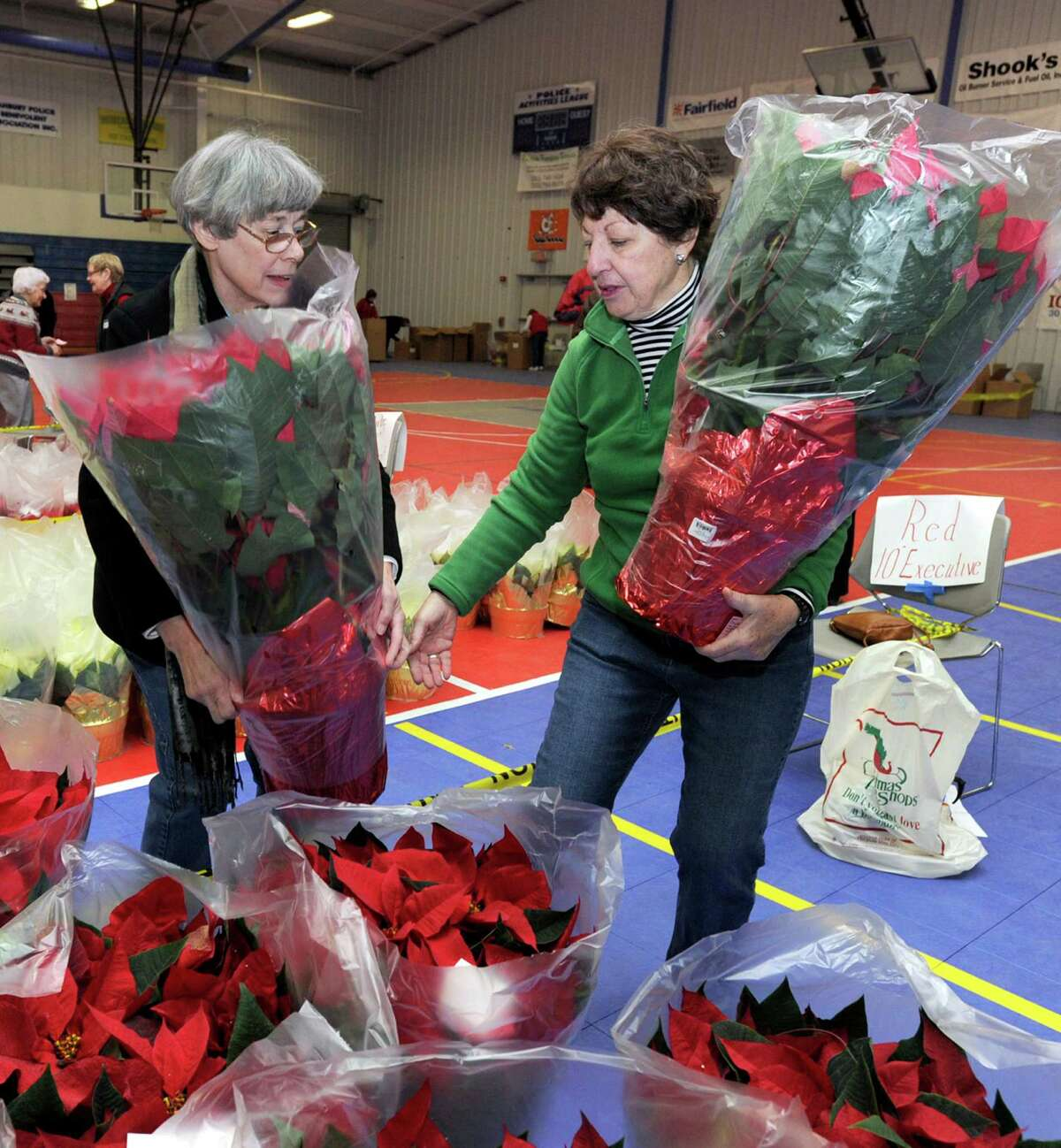 Marilyn Chisholm, left, and MaryEllen Ryder, both of Danbury, carry poinsettias that are being organized for delivery. Members of the Danbury/New Fairfield Woman's Club and Danbury Men's Club met at the PAL building in Danbury Tuesday morning, Nov. 27, 2012, to distribute poinsettias that they sold as a fundraiser.