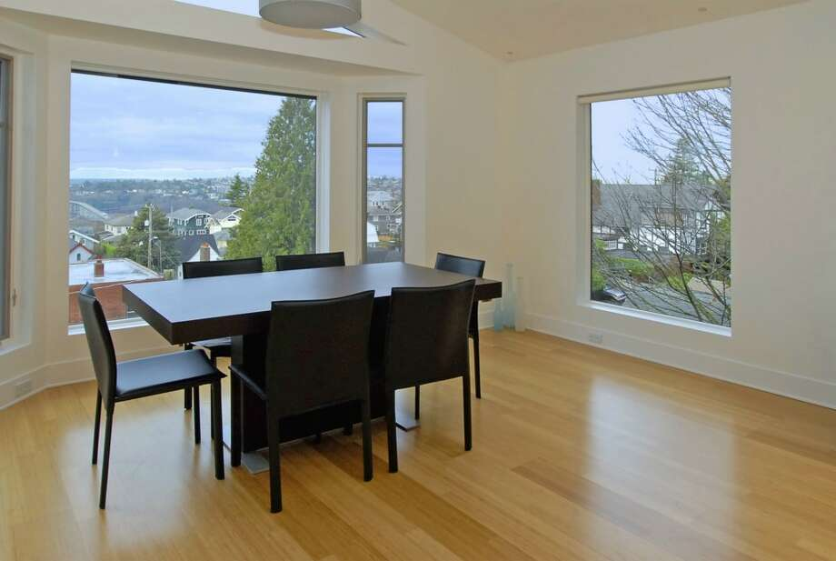 Dining room of 1417 9th Ave. W., Unit 3. The 2,150-square-foot condo, built in 2005 inside an older home, has two bedrooms, two bathrooms, 16-foot ceilings, a den, a library wall and a wall of windows with views of Puget Sound and the Olympic Mountains. It's listed for $1,300,000. Photo: Courtesy Betty Chandler/Windermere Real Estate