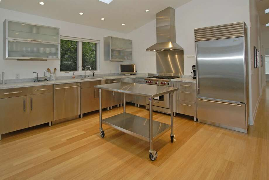 Kitchen of 1417 9th Ave. W., Unit 3. The 2,150-square-foot condo, built in 2005 inside an older home, has two bedrooms, two bathrooms, 16-foot ceilings, a den, a library wall and a wall of windows with views of Puget Sound and the Olympic Mountains. It's listed for $1,300,000. Photo: Courtesy Betty Chandler/Windermere Real Estate