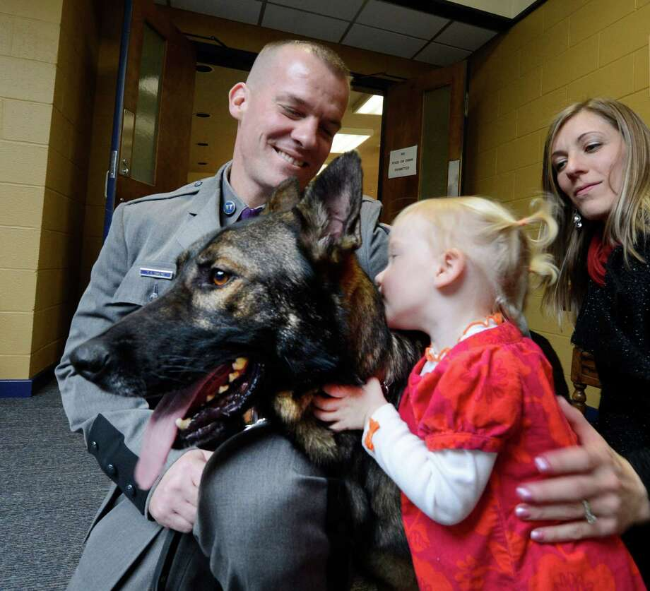K-9 Trooper Ceer gets a hug from Reese Darling as her father Trooper Patrick Darling, left and her mom Erica Darling look on after the K-9 graduation was held at the State Police Academy in Albany, N.Y. Nov 27, 2012.  The K-9 team of Darling and Ceer will be stationed at Troop G in Latham.       (Skip Dickstein/Times Union) Photo: Skip Dickstein / 00020246B