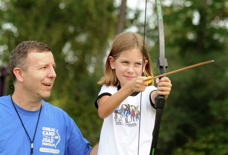 Archery instructor James Stilwell of The Woodlands gives aiming tips to Girl Scout Sarah Lane. Stilwell has been coaching The Woodlands Girl Scout troop in archery for several years. The Girl Scouts of San Jacinto Council has been teaching girls how to hit the bulls-eye for the past 13 years with its Archers in Motion Program. Photo: David Hopper, Freelance / freelance