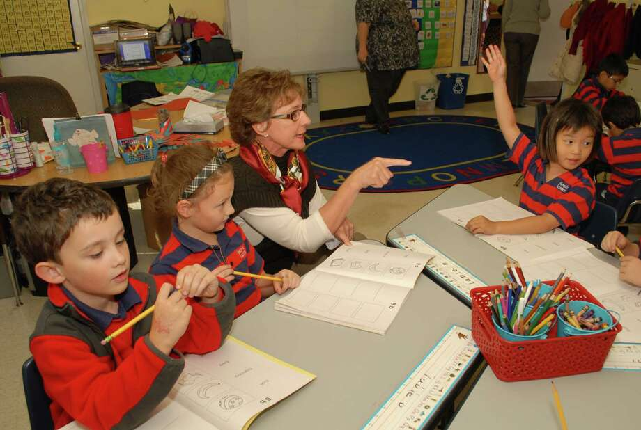 Yorkshire Academy founder Shirley Swinbank works with kindergarteners Griffin Ferguson, left, Holly Payne and Stacy Wee. / Freelance