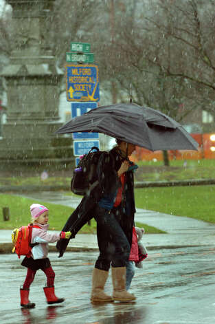 Tori Lawlor, of Milford, makes her way to the train station with her children Addi, 3, left, and Cali, 2,  in tow along North Broad Street in Milford, Conn. on Tuesday November 27, 2012. Photo: Christian Abraham / Connecticut Post