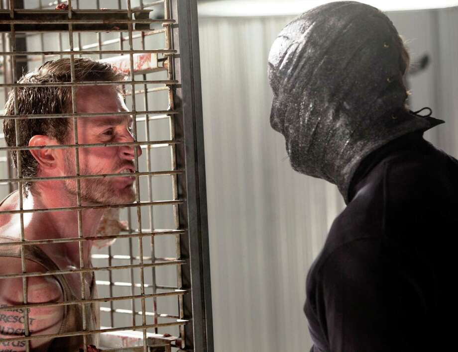 """A scene from the 2012 horror film """"The Collection,"""" starring Josh Stewart (left) and Randall Archer as The Collector in """"The Collection."""" Photo: LD Entertainment"""