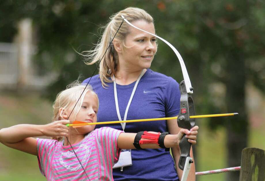 Girl Scout troop leader Jeri Braswell, of Cypress, instructs Hannah Elliott during an archery class at Camp Agnes Arnold in  Conroe. The Girl Scouts of San Jacinto Council have been teaching girls for the past 15 years with its Archers in Motion program.  Photo by David Hopper Photo: David Hopper, Freelance / freelance