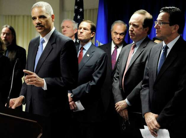 U.S. Attorney General Eric Holder, left, speaks at a news conference to announce a new effort to reduce gun violence in the state's major cities in New Haven, Conn., Tuesday, Nov. 27, 2012. The nation's top prosecutor and other officials have announced a new effort to reduce gun violence in the Connecticut major cities by directly engaging violent groups. Photo: Jessica Hill, Jessica Hill/Associated Press / Associated Press
