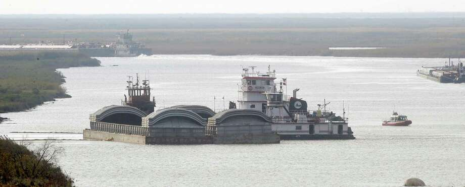 The U.S. Coast Guard and the Port Arthur Fire Department battled a 12-hour plus fire on a tugboat, far left behind the barge, on the Intracoastal Waterway near the West Port Arthur Bridge. The U. S. Coast Guard boat, right could be seen from on top of the bridge patrolling the area.  Four crew members were on board the tugboat when the fire began in the engine room and then spread to the other parts of the vessel, the U.S. Coast reported. The crew members were taken to a local area hospital as a precautionary measure, and the fire is currently under investigation by the U.S. Coast Guard.   Dave Ryan/The Enterprise