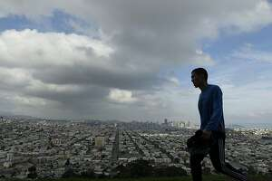A man walks along Bernal Heights Hill under fog and clouds in San Francisco, Tuesday, Nov. 27, 2012. Northern California residents are bracing for gusty winds, rain and snow at higher elevations, as a series of storms gets set to touch down. The rain and snow should begin falling Wednesday and continue through Sunday, according to the National Weather Service. (AP Photo/Jeff Chiu)