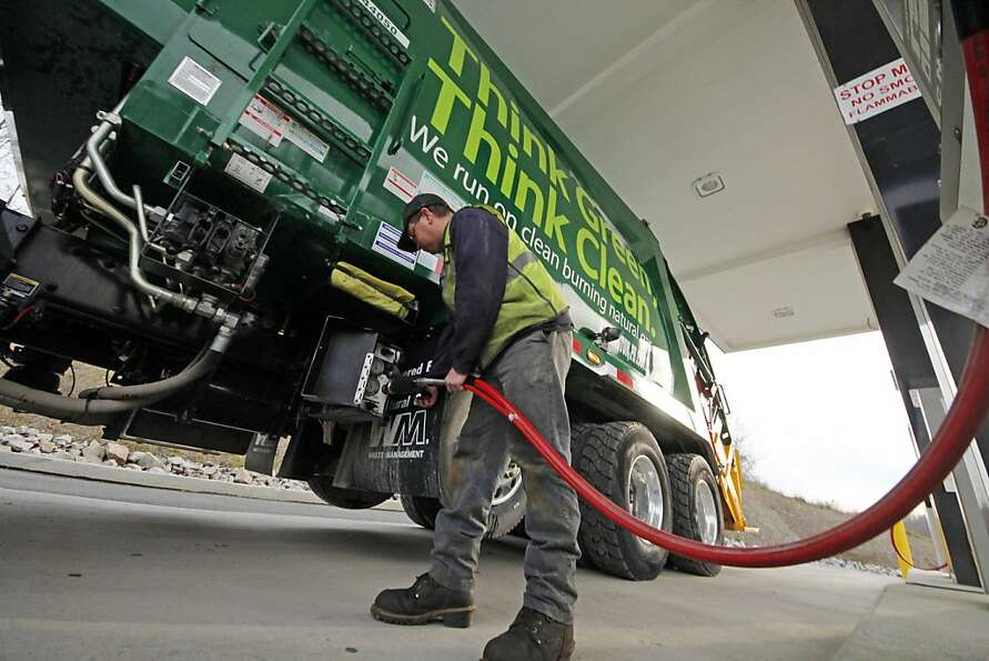 Waste Management driver Alan Sadler fills his truck with CNG gas at the company's filling station in