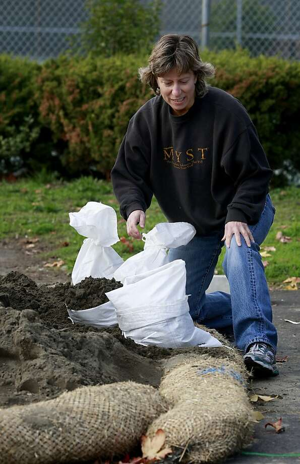 Cece Ritchie of San Anselmo wrestles with some sand bags for her and her parents home nearby.A series of winter storms with wind and plenty of rain through the rest of the week is raising flood concerns in Marin County, Calif. Tuesday November 27, 2012. Photo: Brant Ward, The Chronicle