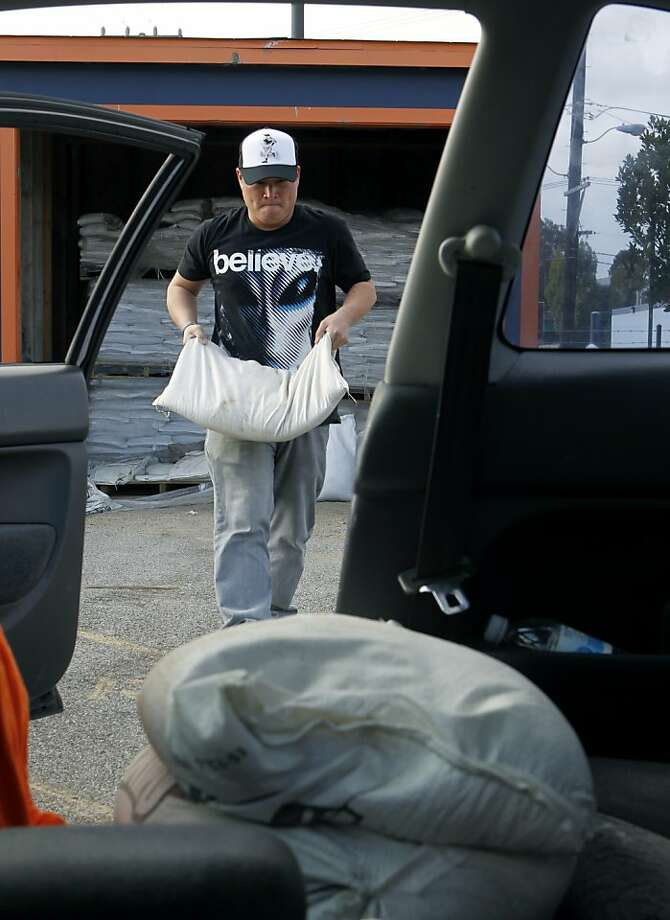 Derrick Doo carries sand bags to his car at the Department of Public Works maintenance yard in San Francisco, Calif. on Tuesday, Nov. 27, 2012 to prepare for this week's predicted rainstorms. City residents are allowed to take up to 10 sand bags per visit. Doo's not taking any chances after his home near Twin Peaks took on 6 inches of water in the last heavy downpour. Photo: Paul Chinn, The Chronicle