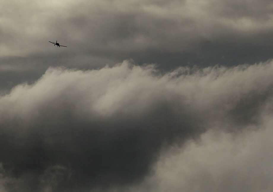 A small aircraft flies among the incoming storm clouds over San Francisco, Calif., on Tuesday, November 27, 2012. The San Francisco Bay Area will be hit by a series of storms starting Wednesday, that will last through Sunday, and could deliver several inches of rain to the region. Photo: Carlos Avila Gonzalez, The Chronicle