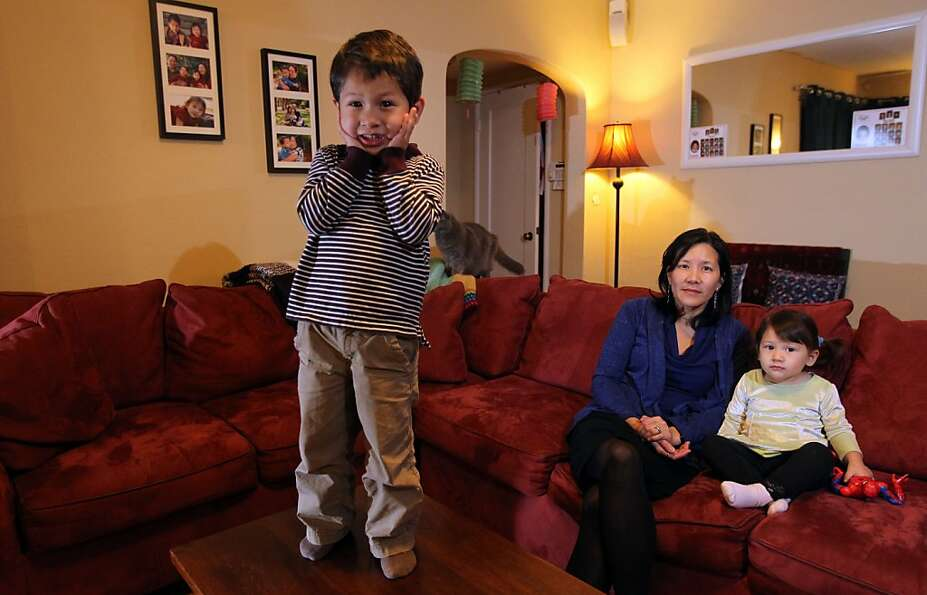 Sue Chiang sits in her family's Oakland home with children Elena Pazy Miño, 2, and Gabe Pazy Miño,