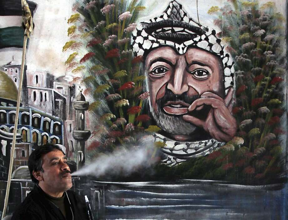 A man smokes near a mural of Yasser Arafat in the West Bank town of Jenin. The Palestinian leader's death in 2004 has led to speculation that he was poisoned with polonium-210 by Israel. Photo: Mohammed Ballas, Associated Press