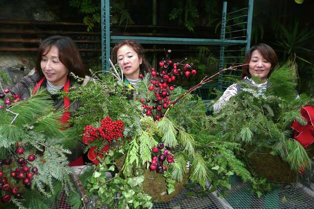 Volunteers turn pine boughs, cranberries and red ribbons into colorful hanging Christmas baskets. Photo: Anne W. Semmes
