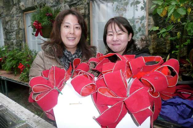 Yukiko Ikeda, left, and Toshie Shoji brought some serious ribbon-tying skills to their first year volunteering out with Greenwich Green & Clean. Photo: Anne W. Semmes