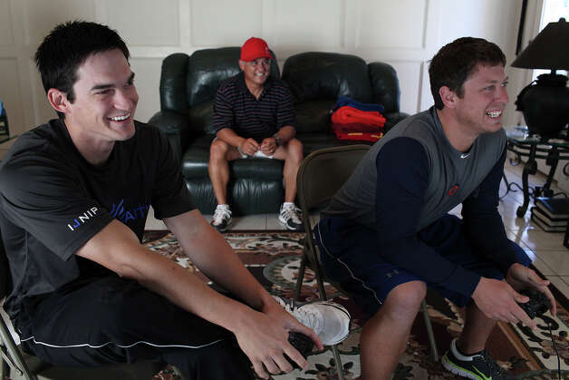 Anthony Vasquez, left, plays Madden NFL on PlayStation with his friend, James Keithley, while Vasquez's father, Rudy Vasquez, watches at their home in San Antonio on Tuesday, Nov. 27, 2012. Anthony and James have been friends since age 11 and played baseball together, including at Reagan High School, until going to separate universities when they played their first game against each other. Photo: Lisa Krantz, San Antonio Express-News / © 2012 San Antonio Express-News