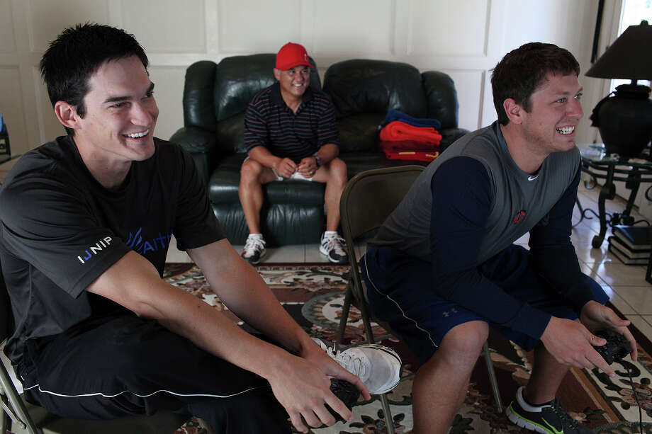 Anthony Vasquez (left) plays a video game with a longtime friend, James Keithley, as the pitcher's father, Rudy Vasquez, watches at their home in San Antonio. Photo: Lisa Krantz, San Antonio Express-News / © 2012 San Antonio Express-News