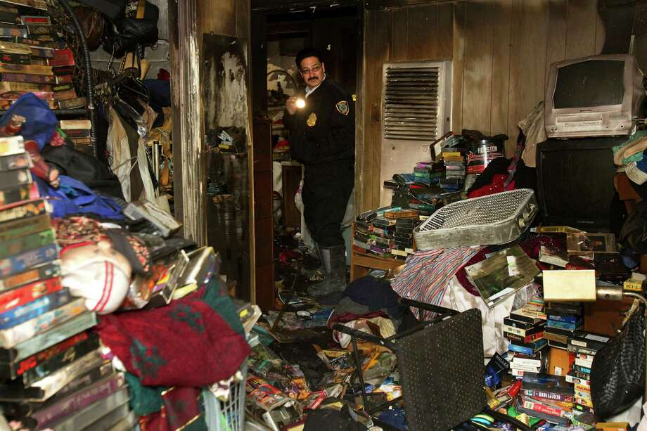 An investigator looks at a home after a fire erupted late Monday night in the 6100 block of Sherwood near Tolnay,Tuesday, Nov. 27, 2012, in Houston. Police said firefighters found a woman in the bathtub while they battled the fire. She was rushed to Memorial Hermann hospital, where she was pronounced dead. Officials said she was believed to be in her 70s. Photo: Cody Duty, Houston Chronicle / © 2012 Houston Chronicle